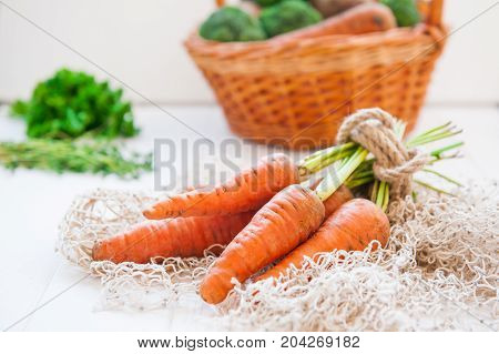 Bunch Of Fresh Organic Dirty Carrots From Farm Market On The White Wooden Background. Vegetables. He