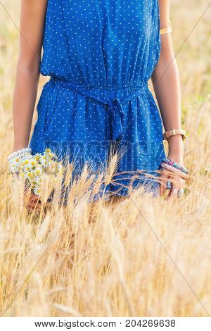 Girl enjoying in a wheat-field with bouquet of flowers.