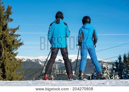 Man And Woman Skiers Standing On Mountain Top Together Enjoying Beautiful Mountain Landscape On A Wi