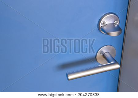 Metalic door knob with lock on a blue door. Horizontal