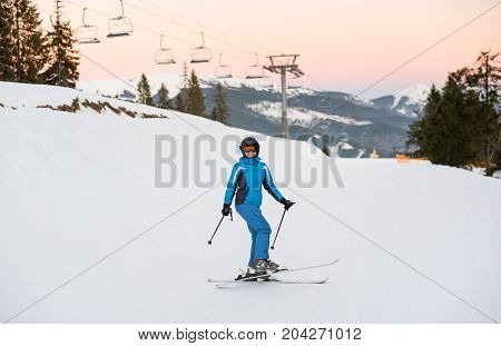 Girl On Skis In Soft Snow In The Mountains Wearing Helmet, Blue Ski Suit And Goggles. Winter Sports