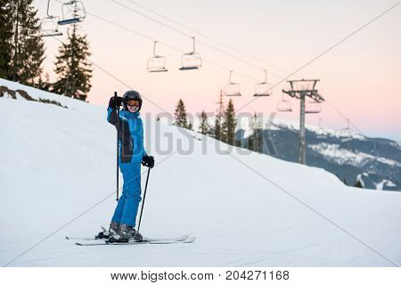 Woman Skier Standing In Snow Mountain And Showing Thumbs Up Gestures Of Good Class Against A Ski-lif