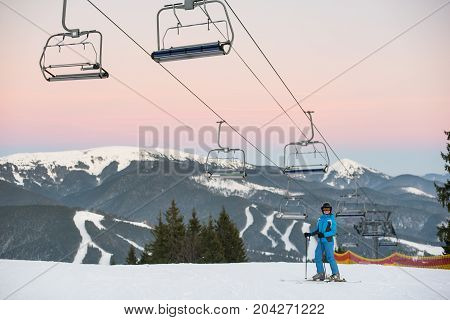 Sport Woman In Blue Winter Clothes, Helmet And Goggles Holds Sticks In Hand On A Background Of Ski R