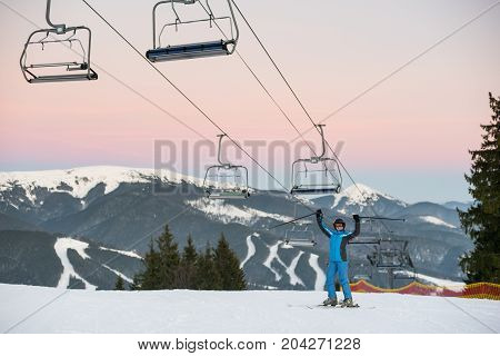 Skier Woman In Blue Winter Clothes, Helmet And Goggles Raised Sticks Up Standing Under Ski-lift On A