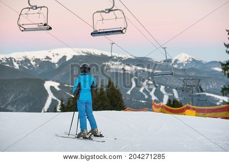 Girl In A Blue Ski Suit And A Helmet Stands On The Skis Under The Ski-lift With Her Back To The Came