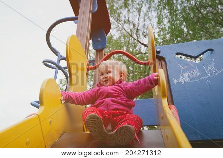 cute little girl playing on playground outdoors, kids development