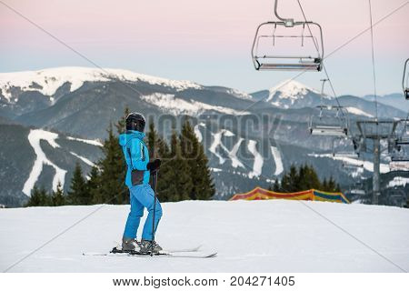 Woman Skier On Slope In The Mountains Of Winter Resort. Woman At Ski Resort Wearing Helmet, Blue Ski