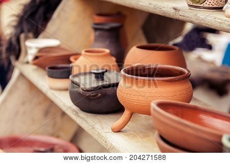 Different Handmade Pottery On A Wooden Shelf