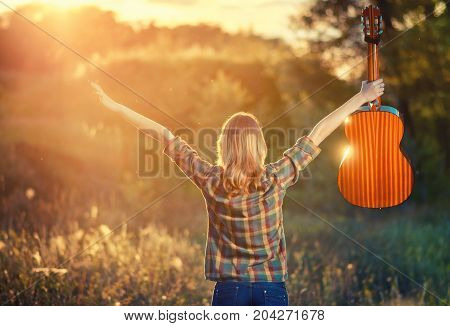Young Girl In A Plaid Shirt At Sunset With An Acoustic Guitar