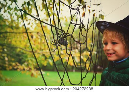 halloween celebration- little boy with spider web play in nature