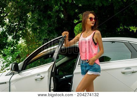 attractive fashion Lady in glasses and short shorts opens the car door and looks away
