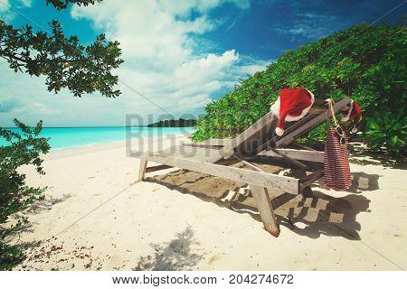 Christmas on beach -chair lounges with Santa hats at sea beach