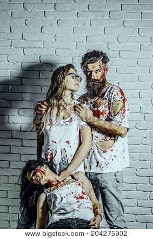 Halloween people on white brick wall. Bloody hipster and two girls in torn clothes. Vampire man and women with red blood. Halloween holiday celebration concept