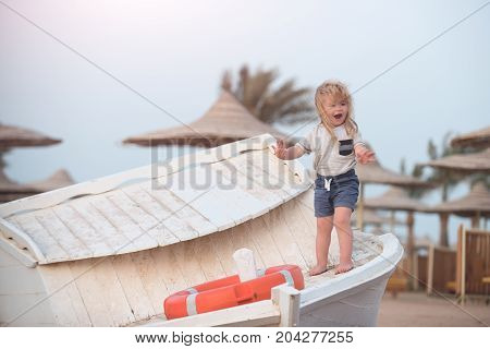 Kid small boy with delighted expressive emotions on adorable face with long blond hair in white shirt and blue shorts standing near orange life ring on wooden boat at coast