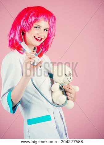 Happy nurse smiling in red wig on pink background. Doctor and patient. Health care and cure concept. Girl curing teddy bear toy with syringe. Woman wearing medical uniform with stethoscope.