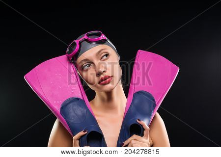 A woman swimmer holds fins for the pool