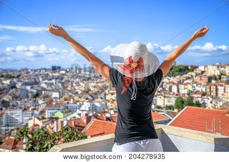 Aerial view of Lisbon, Portugal, from the highest point in the city. Happy tourist woman with open arms admiring Lisbon panorama from Miradouro da Nossa Senhora do Monte in Alfama district at sunset.