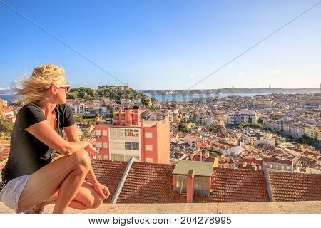Aerial view of Lisbon, Portugal, from the highest point in the city. Caucasian woman looking Lisbon panorama from viewpoint Our Lady of Mt. in Alfama district at sunset. Tourism and travel concept.