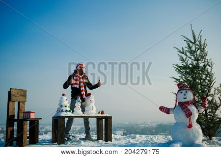 Man With Snowy Sculptures And Presents On Table And Chair