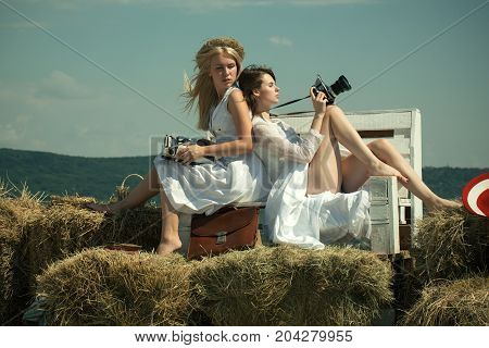 Brunette girl with camera. Hobby and lifestyle. Summer vacation concept. Girlfriends sitting on bench on blue sky. Blond woman with vintage typewriter.