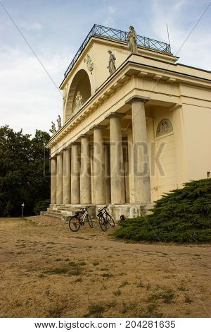 View on the Apollo temple in the Czech republic. On the background is blue sky with white clouds. Trees and bushes. There are two bikes in front of the temple.
