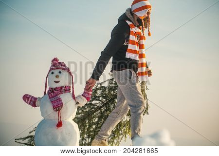 Guy And Snow Sculpture Wearing Hats And Scarves