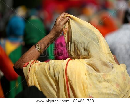 elderly woman with headscarf and hand during a religious ceremony outdoors