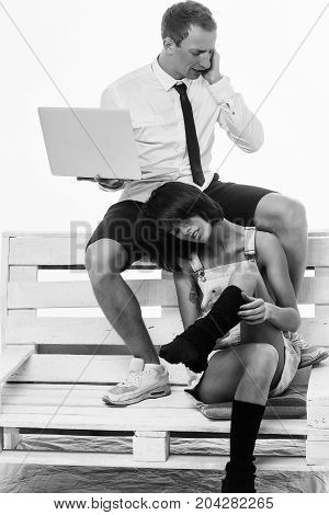 young couple of handsome busy man speaks on cell phone or businessman and pretty woman or girl working on portable laptop in shirt and tie sits on wooden bench at home isolated on white background