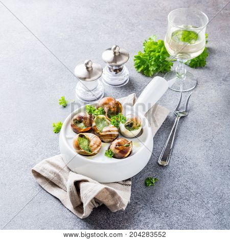 Bourgogne Escargot Snails with garlic herbs butter in white pan on light gray background. Healthy food concept with copy space.