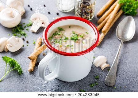 White enamel mug with delicious homemade mushrooms champignons soup with parsley. Healthy food concept.