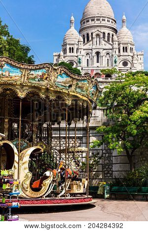 Paris France - June 22 2017: Vintage carousel (merry-go-round) and Basilica Sacre Coeur on Montmartre hill in the sunny summer day.