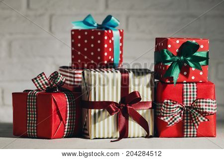 Background of composed Christmas giftboxes wrapped with paper and ribbons on white background.