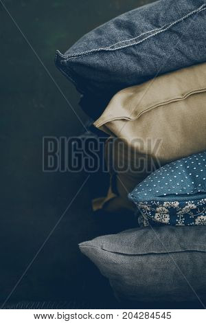 Background of assorted fabric pillow lying in stack on black background.