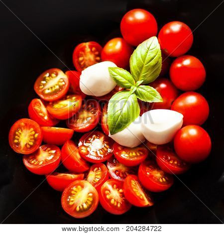 Food ingredients - Fresh Tomato basil leaf mozarella cheese. Fresh vegetables and herbs over dark chalk board background. Healthy food diet nutrition concept.