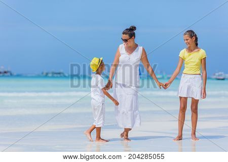 Family of three - mother with his child having fun at the beach