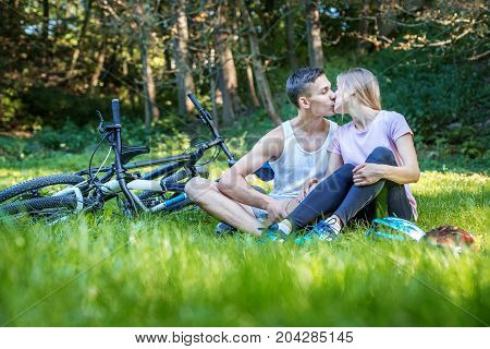 Young happy couple in love kissing. Walking in the park on bicycles. The concept of cycling and a healthy lifestyle and love.