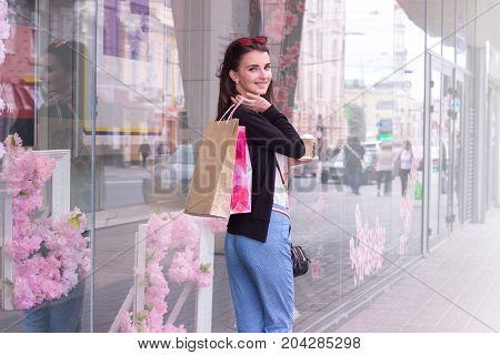 charming happy girl is standing on the street with shopping and looking at the camera