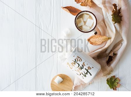 Fall still life with yellow leaves, coffe with marshmallows and warm plaid, cozy autumn flat lay on white wooden background