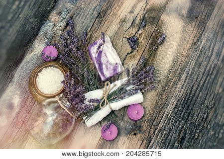 Spa concept - lavender soap, scented salt and dry lavender on rustic wooden table