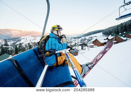 Skier Man Sitting At Ski Chair Lift In Beautiful Day Looking And Thoughtfully Into The Distance. Clo
