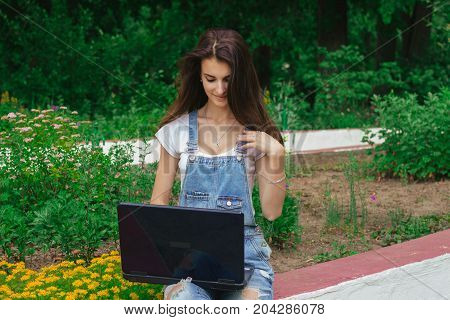 cute young brunette girl using a laptop outdoors