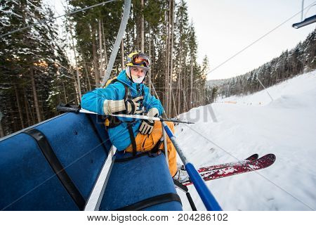 Professional Skier With Skis Sitting At Ski Chair Lift Looking At The Camera Riding To The Top To Ge