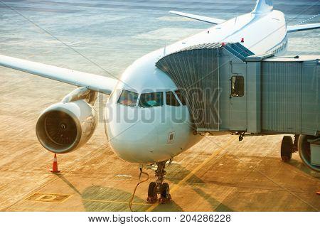airplane preparing to take off at the airport, passenger boarding bridge attached to the aircraft.