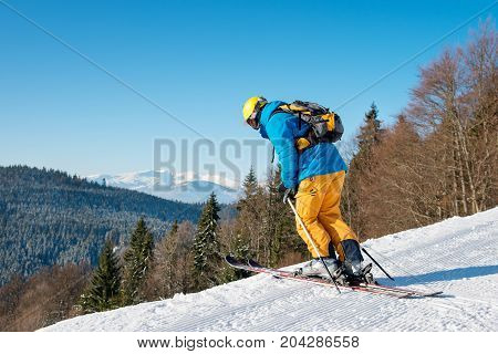 Rearview Shot Of A Skier In Colorful Gear Skiing On Powder Snow In The Mountains Copyspace