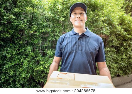 Handsome Young Asian Delivery Man Smiling While Holding A Cardboard Box Delivery To His Customer.