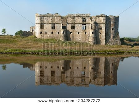 Carew Castle, Pembrokeshire. Carew Castle overlooks the tidal mill pond on the Carew River. The north face of the Norman castle was later transformed into an Elizabethan mansion