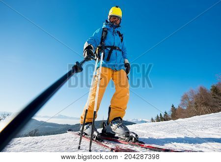 Low Angle Shot Of A Male Skier Taking A Selfie Using Selfie Stick Posing On Top Of A Slope At The Wi