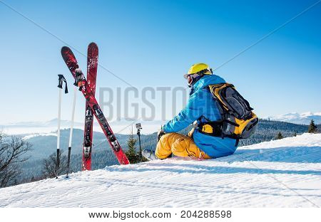 Rearview Shot Of A Skier Sitting On Top Of The Mountain Near His Skiing Equipment Relaxing Enjoying