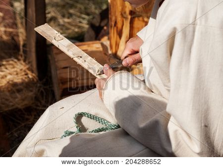 Carpenter Working With Wooden Plank With Sharp Knife