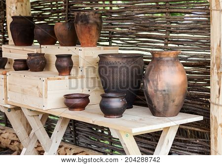 Different Ceramic Pots On A Wooden Table Near Wicker Wall